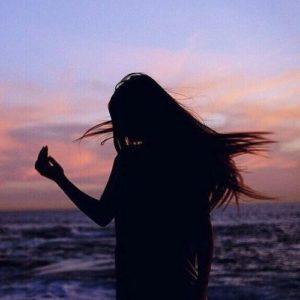 海を一人で歩く女性