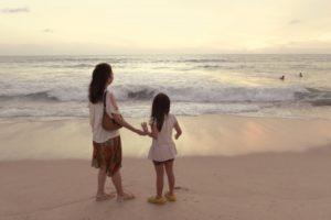 海岸を歩く子供と母親